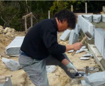 坂石材代表が墓石の加工中